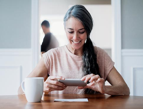 Woman taking photo of check with phone at dining table.