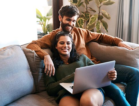 Young couple on laptop at home.